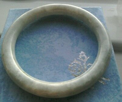 Jade bangle. Pale greenish white mottled. 63mm inner diameter. Fit average wrist