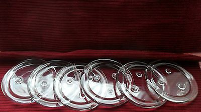 Set of six round clear glass coasters with raised rims