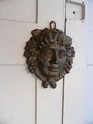 Antique cast iron wall mounted plaque of face
