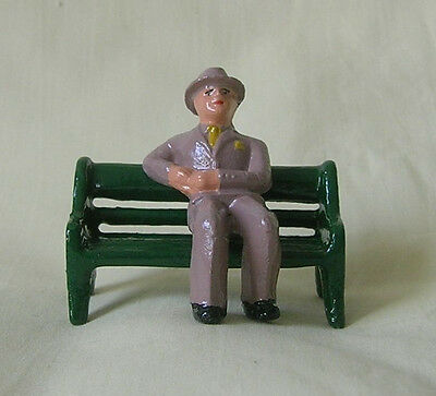 Businessman in suit sitting on park bench, Standard Gauge model train layout