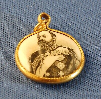 An unusual early celluloid pendant featuring King Edward VII and Queen Alexandra