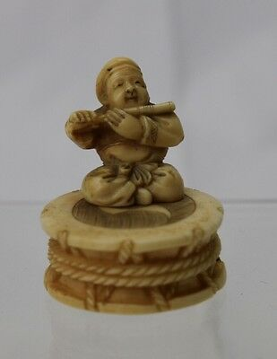 A japanese stag antler netsuke of Daikoku playing a flute. Meiji period