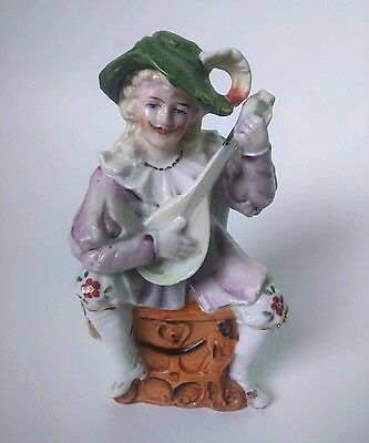 Pottery Harlequin Playing A Mandolin on a chair