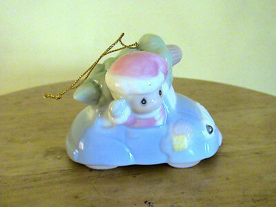 Pastel Child With A Pink Hat In A Blue Car With A Green Christmas Tree Ornament