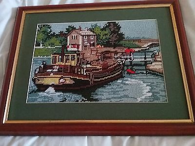 completed framed tapestry of barge on river