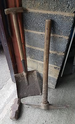 Pick axe with wooden handle, sledge hammer head and builders shovel.