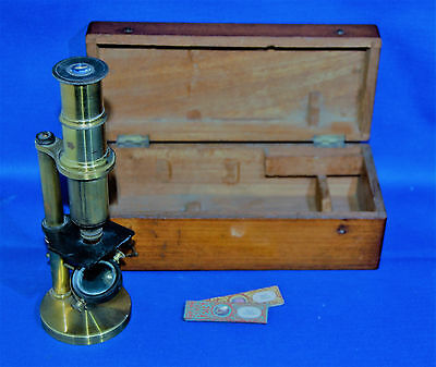 A super antique brass bodied pillar microscope, two attached lenses, box, slides