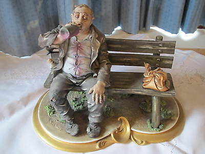 Vintage Capodimonte Figurine. Tramp sitting on a bench and drinking from bottle.