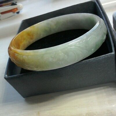 Childs jade bangle. Chinese jade with bats, fish and money. 55/57mm diameter.
