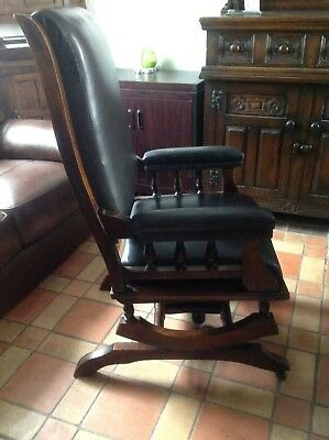 An old, wooden, leather upholstered rocking chair