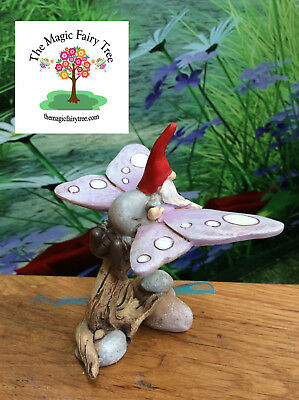 Garden gnome riding butterfly figurine