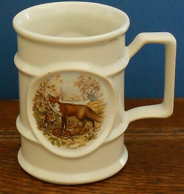 A Holkham Pottery tankard Mug with fox and cubs design.