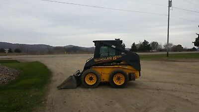 New Holland LS 160 skid steer with attachments (brush hog, new pallet forks)