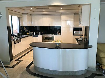 White poly kitchen with integrated fridge panelling and black granite benchtops