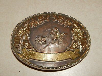 Belt Buckle Looks Like Brass Or Copper With Silver.  Has A Cowboy Roping A Calf.