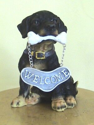 Cute Dog With A Bone In His Mouth Holding A Welcome Sign