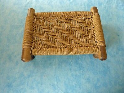 Low wooden footstool with corded woven covering