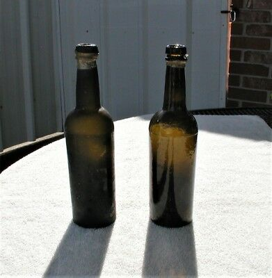 Two Pontil Black Glass Bottles still with some of the lead seal around the lip