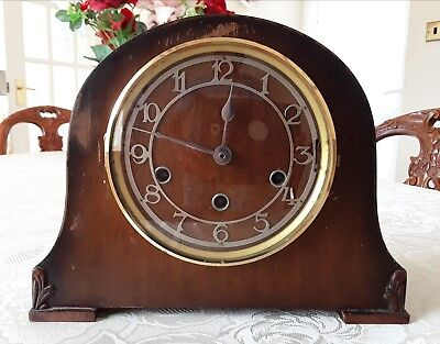 Vintage wind-up wooden mantle chimming clock with key.