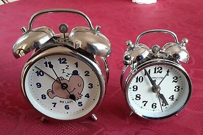 Two chrome wind-up alarm clocks with bells.