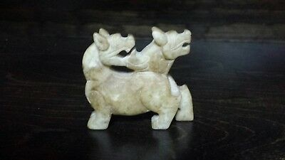 Mythical carved jade animal. Two headed protector. Also a small donut