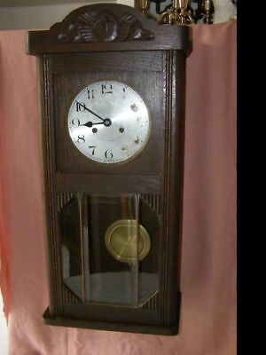 Old wooden wall clock pendulum mechanism