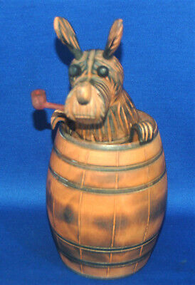 An antique carved wooden Black Forest Scottie dog in barrel tobacco jar