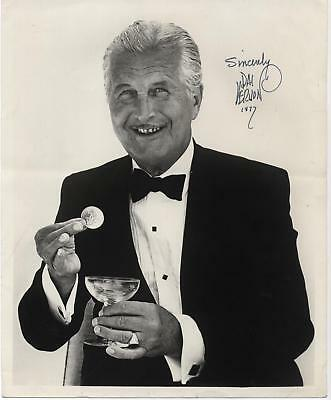 Dai Vernon signed photo dated 1977 of him holding a coin and a glass, smiling