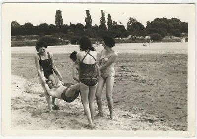 1950s Vintage Snapshot of Women in Swimsuits Swinging a Man on the Beach