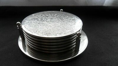 Set of six engraved silver-plated coasters in matching silver-plated caddy.
