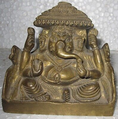 (98). An old or antique  look solid brass statue of a enthroned GANESHA.