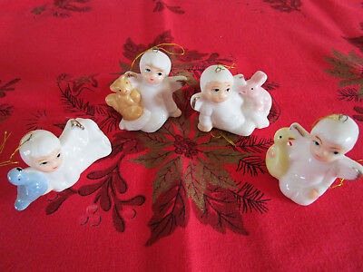 4 Small Angel Ornaments Holding Animals may be Porcelain.