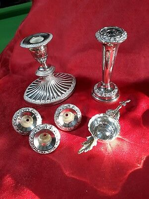 Silver plated:Two ornate candlesticks, 3 x inserts and a decorative tea strainer