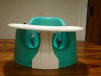 Green Bumbo seat with straps and tray.