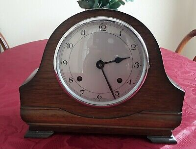 Vintage working wooden wind-up mantle clock with pendulum and key.