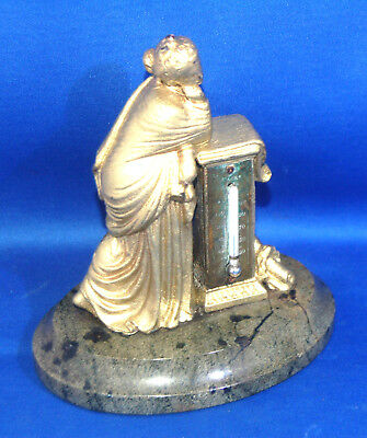 An antique Victorian cast metal desktop thermometer, Calliope, on stone base