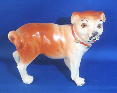 A lovely antique pottery or porcelain figure of a standing pug dog, glass eyes