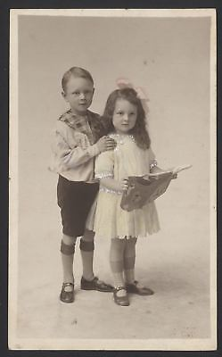 Little Boy Holds His Sister Who Holds Her Open Scrap Book. Tinted Photo Postcard