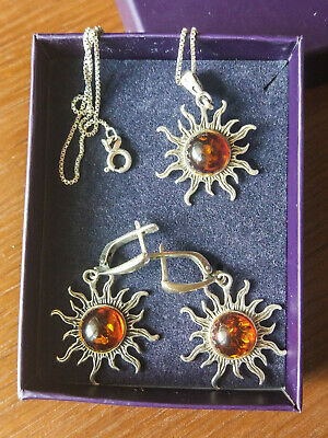 Earrings and pendant in the shape of the sun with natural amber made of silver