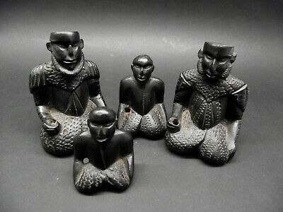 An unusual group of four carved wooden kneeling figures, black wood.