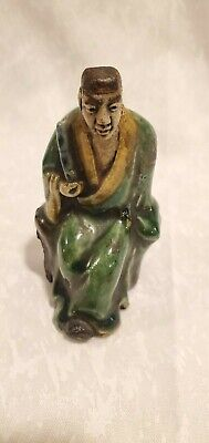 Antique potter mud-man Chinese figurine or aged man in a green and cream glaze