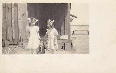 RPPC W two girls with doll in buggy outside 38123