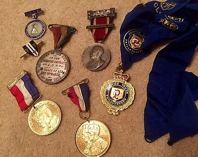 A Collection Of Various Medals And Other Items In An Old Tin