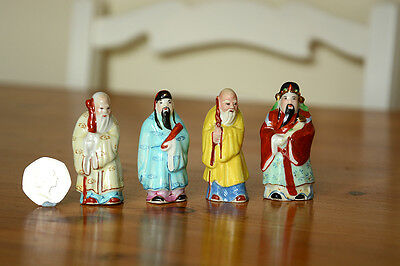 Four small porcelain pottery figurines of Chinese men in traditional costume.