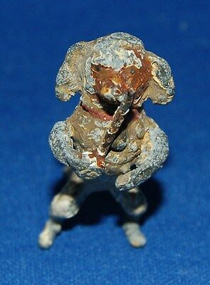 A lovely painted tiny model of a dog (spaniel ?) musician playing a pipe