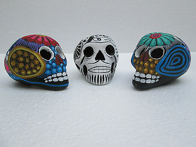 3 HAND PAINTED SKULLS clay pieces  similar to huichol and alebrije