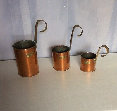 A Set Of Three Vintage Copper And Brass Measuring Pots.