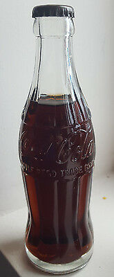 Vintage contoured Coca Cola 'BOTTLE REGD TRADE MARK' bottle. Unopened