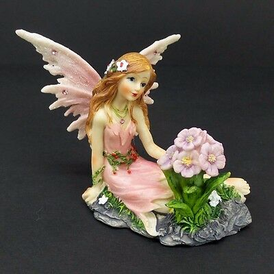 Fairy Figurine in Pink Dress with Glitter Accents Sitting Beside Flowers