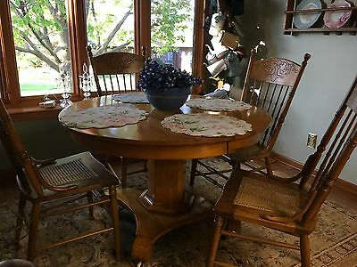 """Antique oak 45"""" table on castors and 4 pressed back caned chairs"""